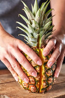 Fresh halves of an exotic pineapple hold the girl's hands on a wooden kitchen board. Vitamin fruit