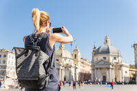 Female tourist with a fashinable vintage hipster backpack taking photo of Piazza del Popolo in Rome, Italy by her mobile phone.