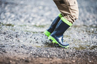 Close up on toddler wearing rubber boots in rainy weather