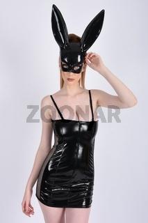 Ashley Foxx, sexy, vollbusige Rothaarige, gekleidet in einem glanzenden schwarzen PVC-Kleid und Mask