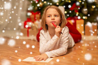girl writing christmas wish list at home