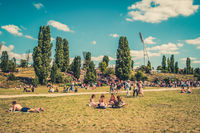 Cityscape blur concept - People enjoying sunny summer day on meadow in crowded Park (Mauerpark)  in Berlin City