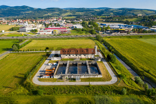Sewage treatment plant in rural area, small town and mountains in background