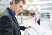 Business Mann liest Tageszeitung im Flughafen