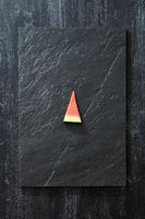 A piece of fresh watermelon on a black slate on a dark concrete background with copy space. Vitamin dessert. Top view
