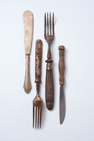 Collection of old metal with wooden handle forks and knives on a gray background with copy space. Vintage set. Flat lay