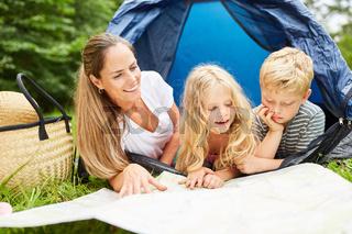 Kinder im Zelt blicken auf eine Landkarte
