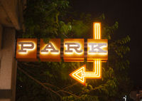 Blue and Orange Neon Sign Says Park Here