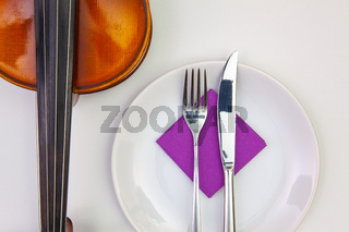 White plate and old violin on the white  wooden table.