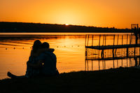 Young couple resting on the river bank
