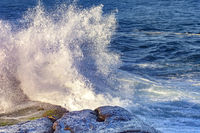 Waves crashing against rocks with spray