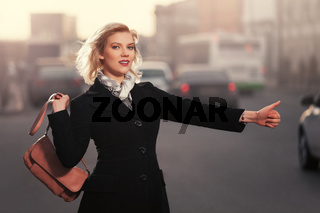 Fashion blond woman in black coat hailing a taxi cab walking in city street