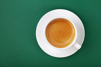 White cup of espresso coffee on saucer on green