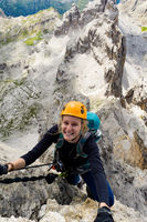 attractive blonde female climber on a steep Via Ferrata in the Italian Dolomites