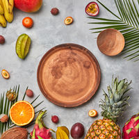 Various juicy exotic fruits, coconut, lychees, carom, pineapple, palm leaves and empty brown wooden plates on a gray concrete background with space for text. Flat lay