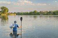 man with paddle standing in water