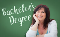 Bachelor's Degree Written On Green Chalkboard Behind Smiling Middle Aged Woman