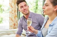 Junge Frau trinkt mit ihrem Freund ein Glas Sekt