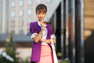 Young fashion business woman in purple blazer and sunglasses walking in city street