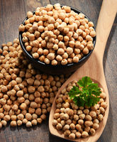 Composition with bowl of chickpeas on wooden table.