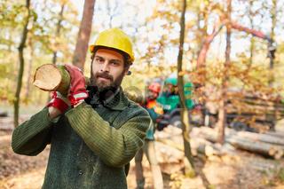 Zwei Waldarbeiter tragen einen Baumstamm