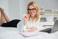 Businesswoman working laptop in bed