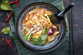 Traditional Thai kaeng phet red curry with vegetables and rice noodles as top view in a wok
