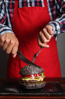 Man cuttung black burger