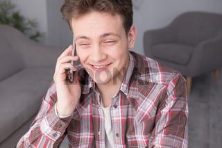 Teenage guy using phone while studying.