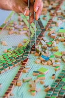Ceramic design. Ceramic mosaic. The man organizes with a tweezers a puzzle of ceramic elements.