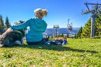 Frau sitzt in der Sonne an einer Seilbahn im Fichtelgebirge