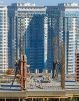 Construction workers work top building
