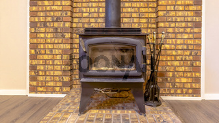 Panorama frame Fireplace inside the room of a home with wood floor and stone brick accent wall