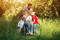 Woman in wheelchair kisses her son among family members