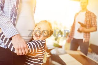 Tochter umarmt schwangere Mutter mit Babybauch