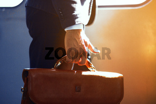 Man holding leather bag while on train.