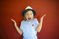Pretty emothional children wear a hat on a red background