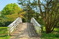 Dutch wooden arch bridge in park during spring