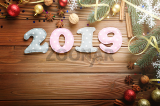 Colorful stitched digits 2019 of polkadot fabric with Christmas decorations flat lyed on wooden background. Space for text