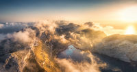 Aerial landscape with mountains and low clouds at sunset