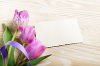 Lilac tulips and blank greeting card on natural wooden background with space for text