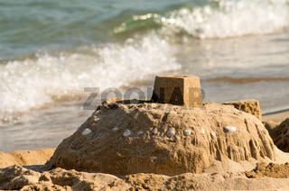 Sand castle on the seashore and a soft blue sea wave.Sunny blue sea
