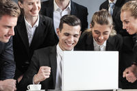 Business team look together at laptop