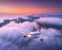 Passenger airplane flying over clouds at sunset. Aircraft