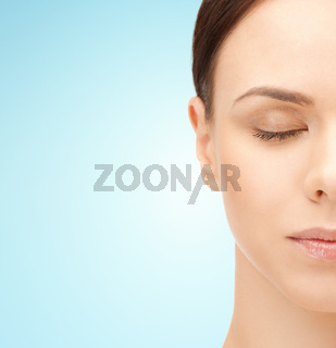 half face of young woman over blue background