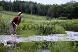 Girl by the river with a fishing rod