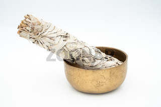 Flat lay composition of dried white sage and wholistic healing Tibetan singing bowls