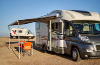 Empty folding chairs and table under canopy near new modern recreational vehicle camper trailer. Adventure