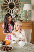 Beautiful daughter gently hugs her senior mother who sits at the table