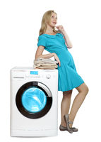 happy young woman in a bright dress joyfully looks up. Leans on a new washing machine with a stack of clean laundry